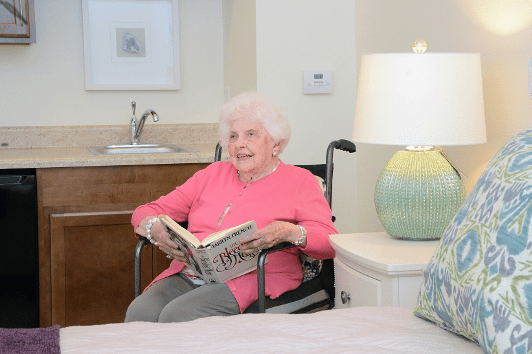Senior woman sitting and reading in her room