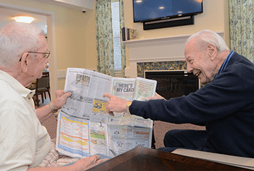 2 senior male friends sharing the newspaper