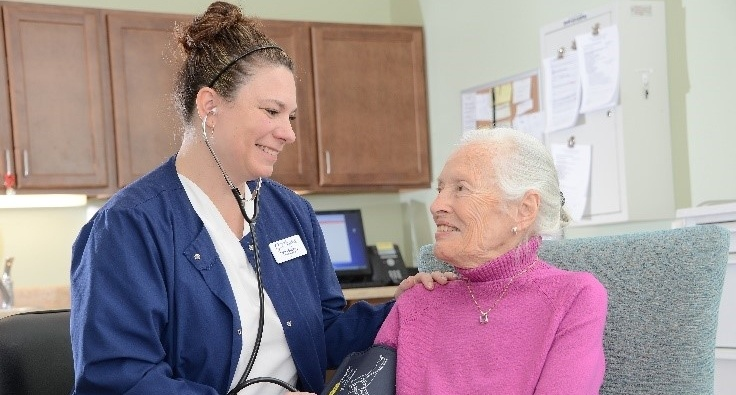 Healthcare worker consulting with senior citizen