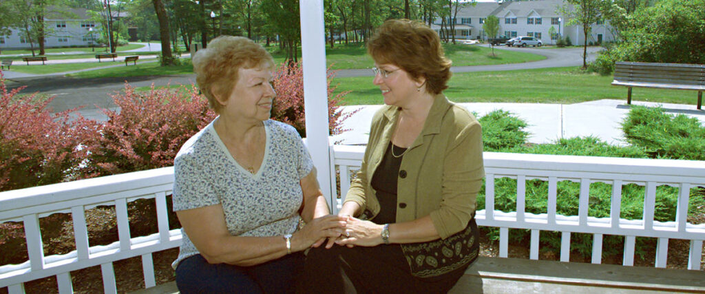 2 women sitting and talking on a porch